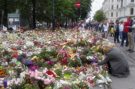 A woman places flowers amongst candles and other floral tributes in memory of the victims of Friday's bomb blast and shooting massacre in Oslo, Norway. (AP Photo/Scanpix Norway/Berit Roald/Scanpix Norway)