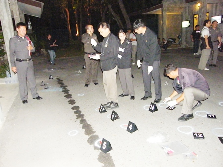 Investigating police begin marking out spots where spent cartridges are being found after the shootout.