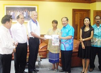 William Macey (center left), representing the Pattaya Sports Club, makes a donation to Mayor Mai Chaiyanit, Nongprue deputy mayors and family to assist families in need.
