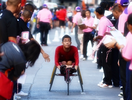 A wheelchair athlete checks his time as he crosses the finish line.
