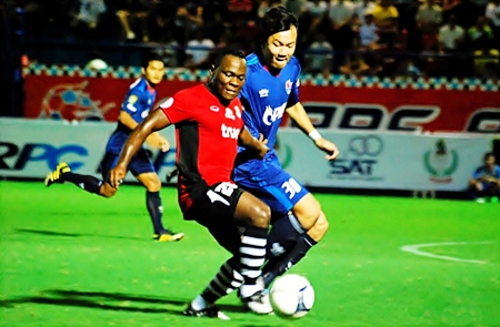Ludovick Takam, center, shields the ball from a PTT Rayong defender during their Toyota Cup match in Rayong, Saturday, July 2. (Photo/Ariyawat Nuamsawat)