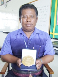 Pitak Sritang, assistant band instructor of Pattaya City School 4, and one of the Pattaya City School Band instructors, shows off the gold medal from the competition.