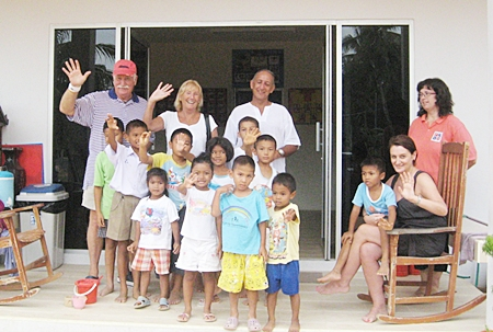 "John & Wendy Khan (center) of ""We2R1"" will be performing Live 60s and 70s music for the Mercy Center Children's Home Grand Opening. Also shown are Mercy family members in front of their ""Forever"" Home Baan Khong Por in Pong."