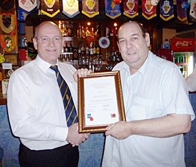 Graham Macdonald, president of the Royal British Legion Thailand presents a certificate of thanks to Bert Elson for the welfare work carried out in Thailand.