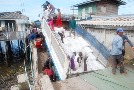 Workers begin removing bags of salt from the overweight truck so that they can eventually pull the truck out and repair the bridge.