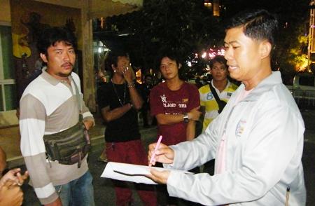 Krit Suwanpiyawong (left) is taken into custody by Maj. Wasu Sangsuksai (right), chief of Pattaya City Hall's regulatory enforcement department.