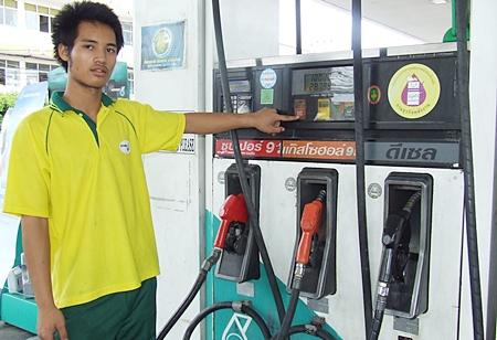 Pathawee Duakhanad, a Petronas pump employee, shows how cheap petrol has become.