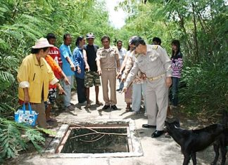 Villagers and officials point to one of the many dangerous uncovered drains in the road after thieves had stolen the cover.