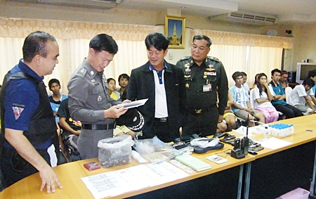Chonburi Gov. Wichit Chatpaisit and high ranking police officials pour over the confiscated paraphernalia, as those arrested sit and wait processing behind them.