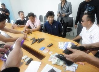 Saksit Suwadit (seated center) is brought in for questioning after police nailed him in a sting operation.