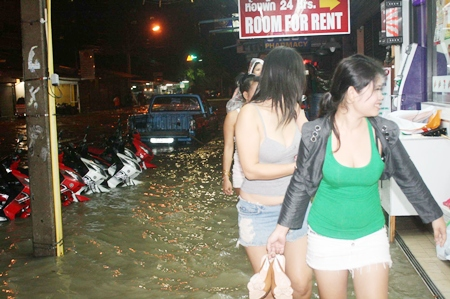 No motorbike taxi here - Women walk past inundated motorcycles as they try to make it home during overnight flooding.
