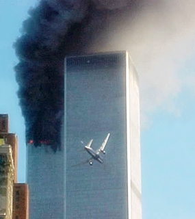 United Airlines Flight 175 approaches the south tower of the World Trade Center in New York shortly before collision as smoke billows from the north tower. (AP Photo/Carmen Taylor)