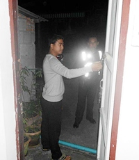 Owner Thanakit Sae-Ung inspects the back door, used by thieves to break into his office.