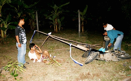 Narong Hinon lays on the ground as police search his motorcycle for drugs.