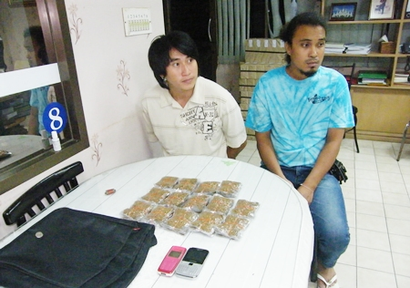 Sinrath Phathasri (left) and Somprasong Chansaard (right) watch as an officer (unseen) weighs one of the packets of marijuana.