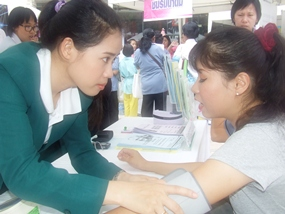 A nurse from Phyathai Sri Hospital checks this woman's blood pressure.