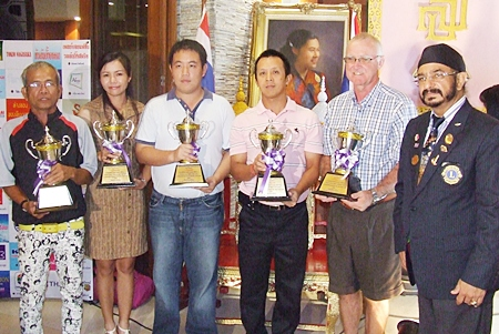 The flight winners of the 20th Sirindhorn's Cup Golf Tournament pose for a photo with Lions Club President-elect of 2011-2012, Montri Sachdev (right).