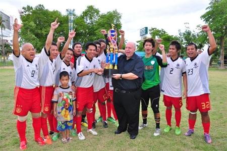"""The winning Siam Sport Deutscher Fußball Fanklub team receive the trophy from Reiner """"Calli"""" Calmund."""
