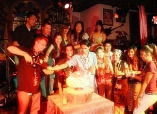 Hotel staff members and guests help cut the cake to mark 10 years of the Hard Rock Hotel Pattaya.