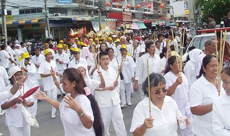 White clad participants in the opening day parade make their way through the streets.