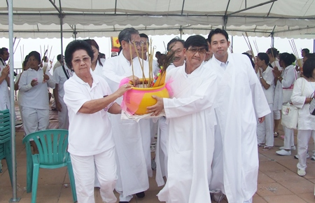 Leaders carry the ceremonial incense pot into the holy ground to pay respects to their deity.