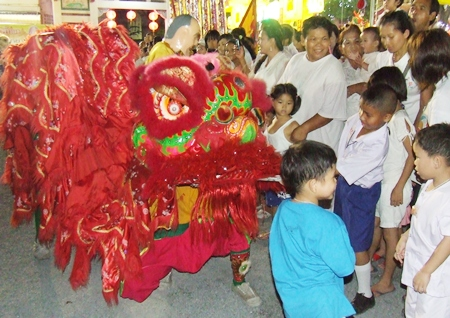 A ferocious red lion excites the youngsters during the festivities.