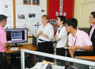 Officials learn how to operate a new passport-scanning machine during a training session in Jomtien Beach.