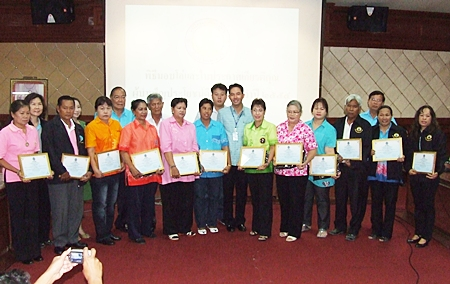 """Mayor Itthiphol Kunplome (center) poses with members of the community that received plaques for their efforts to adhere to HM the King's """"sufficiency economy"""" philosophy."""