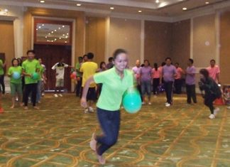 A green team member sprints across the floor in the balloon race.