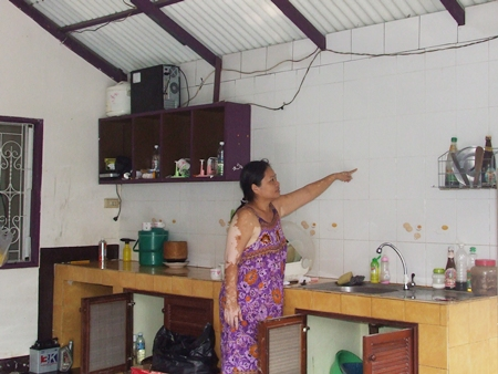 Pa Thongmuan points out how high she said the flood waters reached inside her home.