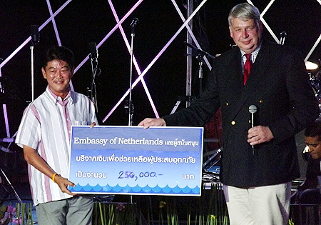 Henk Cor van der Kwast, Deputy Head of Mission at the Dutch Embassy in Bangkok, hands a cheque for 250,000 baht to Chonburi Governor Wichit Chatpaisit (left), to help with the flood relief effort.