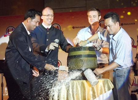 """Mayor Itthipol Kunplome (left) inaugurates the Oktoberfest with the ceremonial tapping of the first barrel of beer. Loud cheers filled the beer hall as the mayor shouted """"O'zapft is!"""" (""""it is tapped!""""). The rest of the evening is history."""