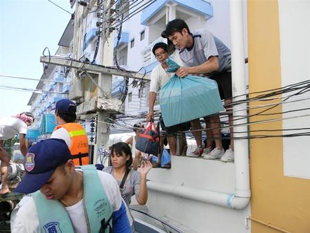 Members of the Sawang Boriboon Foundation evacuate people from upper floors in Nava Nakorn.
