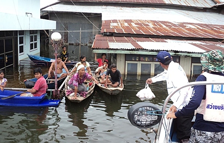 Families reach out for rescue supplies in Ayuthaya.