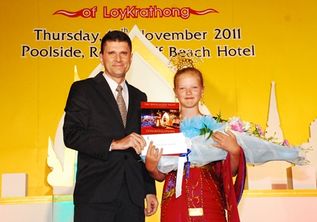 Royal Cliff Hotels Group General Manager Joachim Grill presents Miss Liza from Russia with the award for winning the Best Traditional Dressed Guest competition at the Royal Cliff Beach Hotel.