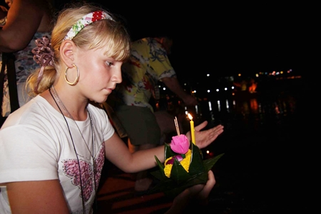 A young woman from Russia makes wish before setting her krathong afloat at Nong Nooch Tropical Garden.