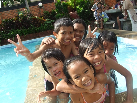 Children are having a great time enjoying the pool.