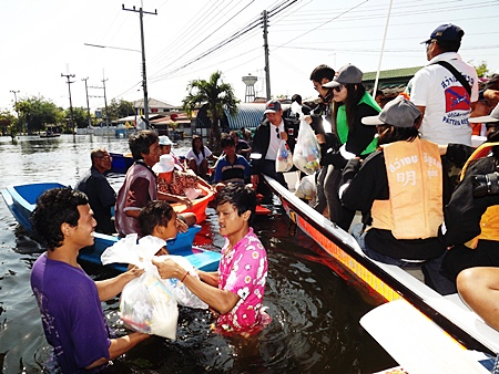 Victims wade through chest deep water to receive aid packages from the Pattaya crew.