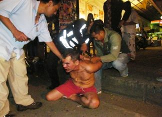 Police and motorcycle taxi drivers wrestle the crazed Russian and put him in handcuffs.