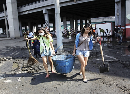 Volunteers carry a bucket full of mud during a clean-up drive after floodwaters receded from Bangkok, Saturday, Nov. 19. Hundreds of city workers, police, army personnel and civilian volunteers have been working to dig out the mud from previously flooded areas in the Big Mango. The situation has improved dramatically in recent days and cleanup has begun in many areas, though some still face weeks more under water. The government said 17 provinces remained flooded Sunday. They also said Sunday that the death toll has reached 602, the majority from drowning. (AP Photo/Altaf Qadri)