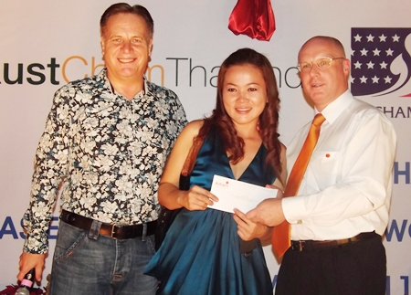 Simon Matthews (left) joins newly elected chairman of the BCCT Eastern seaboard and Amari GM David Cumming (right) in presenting a raffle prize to Anongrat (Som) Corness of Siam Country Club Beauty Supplies.