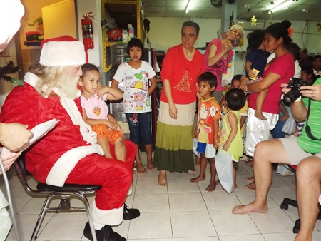 Children wait patiently for their turn to receive a special gift from Santa.