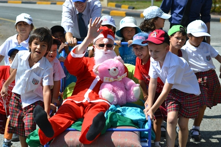 Key stage 1 students pulling Santa around the oval.