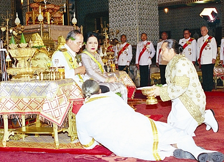 His Majesty the King observes an ancient ritual by receiving lustral water and sacred leaves from the Chief of the Brahmin Court as Her Majesty the Queen looks on at the Grand Palace in Bangkok, Saturday, June 10, 2006.