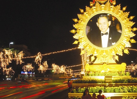 Tail lights from passing vehicles form streaks by a giant portait of His Majesty the King in Bangkok Thursday, Dec. 5, 2002.