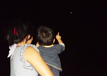 Vanalai Thonsith of Ubon Ratchathani shows her 2-year-old nephew Nong Palm the lunar eclipse from the top of Pratamnak Hill.