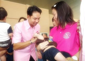 Mayor Itthiphol Kunplome helps a mother give her child some polio vaccine drops.