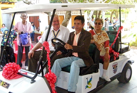 Banglamung Home for the Aged director, Utit Boonchuay sits behind the wheel of the home's new golf cart.