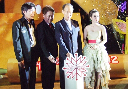 Chonburi Governor Khomsan Ekachai pushes the button to light up the Christmas tree.