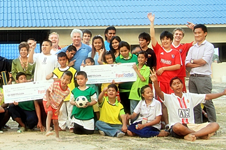Martin Kinsella from Planet Football presents the children from Ban Si Ban Keow with a cheque for 120,000 baht.